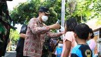 Pj Walikota Makassar Prof Rudy Djamaluddin mengenakan masker kepada anak di Kompleks Lantamal VI Makassar, Jumat 10 Juli 2020. (Ist)